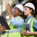image of a man a woman in construction gear and hard hat with clipboard, chatting in a warehouse/industrial plant