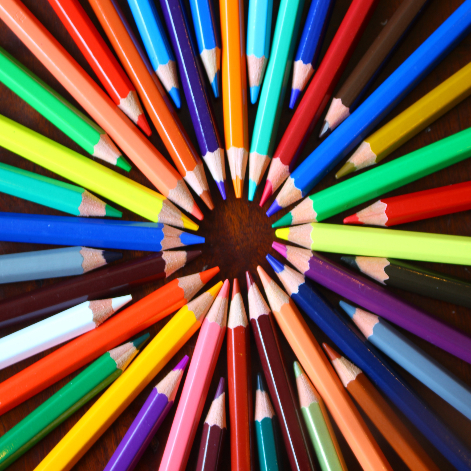 coloured pencils in a circle fan shape on a wood background