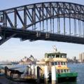 the sydney harbour bridge and a ferry is going underneath