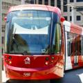 A red oncoming light rail vehicle