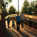 family walking on a bridge at sunset away from the camera