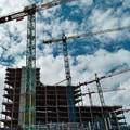 high rise buildings being constructed with cranes surrounding them and blue and grey sky in background